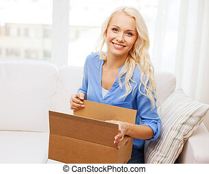 smiling young woman opening cardboard box at home - home,...