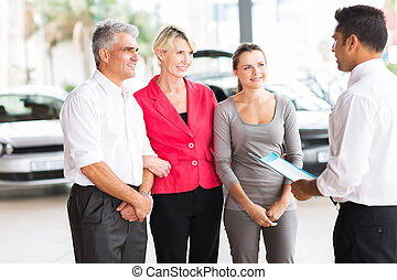 car salesman talking to family in showroom