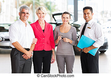 family buying a new car at vehicle dealership - family of...