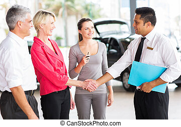 senior woman handshaking with car sales consultant