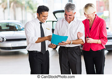 mature couple buying a new car at vehicle showroom