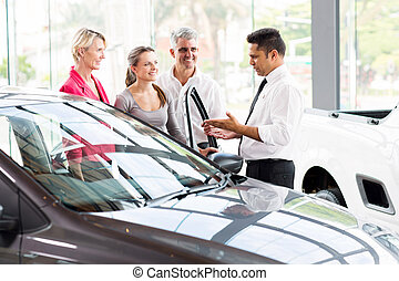 vehicle salesman showing new car to family - vehicle...