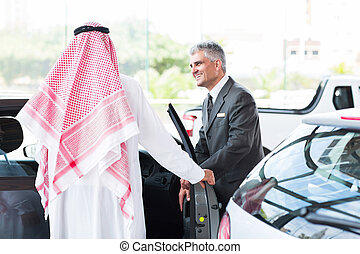 senior car salesman showing a new car to Arabian man