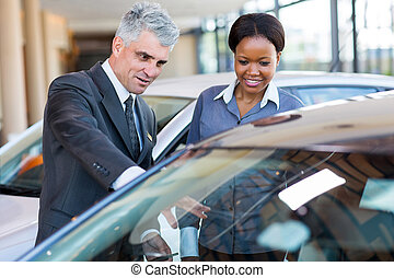 mature car dealer showing new car to african customer -...