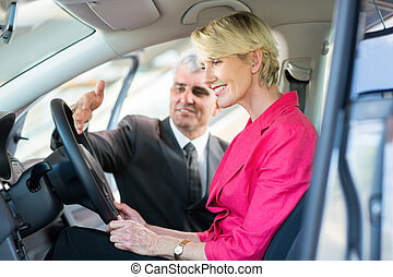 senior car sales consultant showing a new car to customer