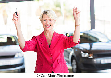 senior woman collecting her new car from dealership -...