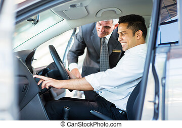 indian man checking car features at showroom - happy indian...