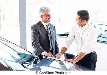 senior car salesman just made a sale to young customer