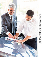 young man signing documents at car dealership with salesman