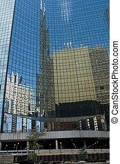 Skyscraper reflecting in mirrored windows