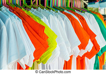 Variety of multicolored shirt clothes hangers in row.