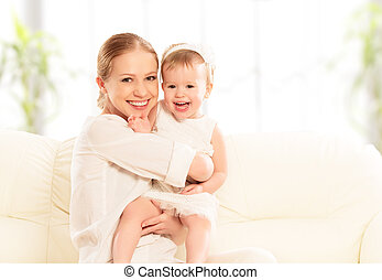 happy family. Mother and baby daughter plays, hugging, kissing at home on the sofa