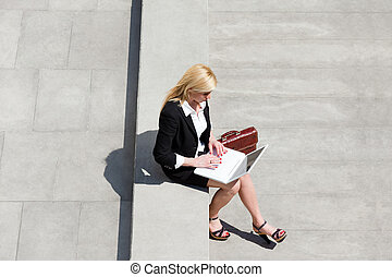 businesswoman using laptop outdoors - high angle view of...