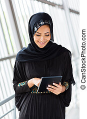 middle eastern woman using tablet computer - happy middle...