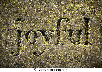 "Joyful - The word ""Joyful"" etched in a old weathered stone."