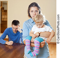 after quarrel at home - Woman with baby against husband...