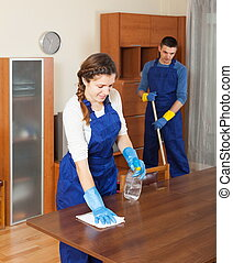 Professional cleaners cleaning furniture and floor in room