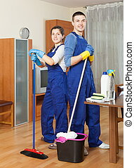 Two happy cleaners cleaning floor
