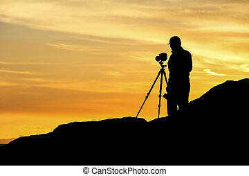 Photographer - Landscape photographer with a tripod mounted...
