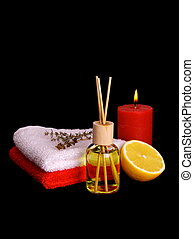 Yellow bottle with essential oil, candle and bath towels