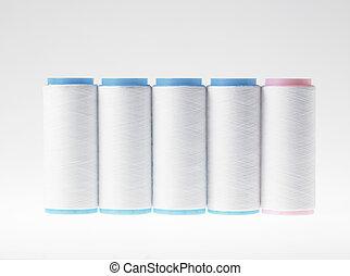 White on white, spools of thread on white background -...