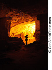 Silhouette of photographer in a cave - Silhouette of...