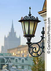 Wall mount street lamp against urban background