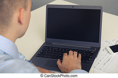 Rear view closeup of a young man working of a laptop