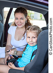 Mother fastening little daughter into infant safety seat in car