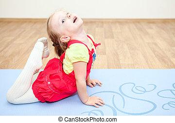 Flexible child making gymnastics on floor