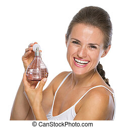 Smiling young woman with perfume bottle