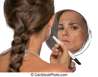 Young woman looking in mirror and plastic surgery marks rear...