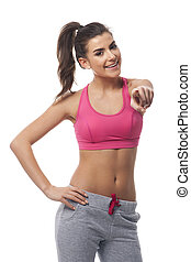 Smiling fitness woman showing at camera side