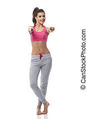 Young fitness woman pointing at camera side