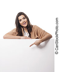 Happy woman pointing at empty whiteboard
