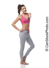 Happy fitness woman showing at camera side