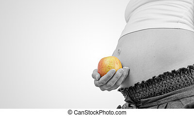 Pregnant woman holding a ripe apple