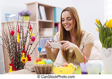 Happy woman taking photo by mobile phone in easter holiday