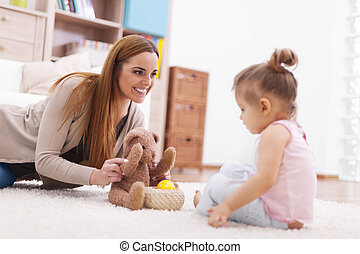 Mother playing with her baby on carpet