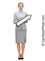 smiling businesswoman with direction arrow sign - business...