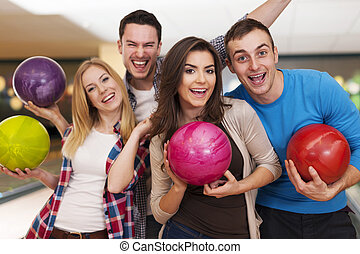 Happy friends bowling together