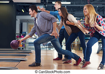 Friends cheering their friend while throwing bowling ball...