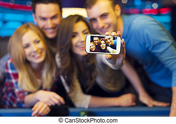 Smiling friends taking selfie photo from nightclub with...