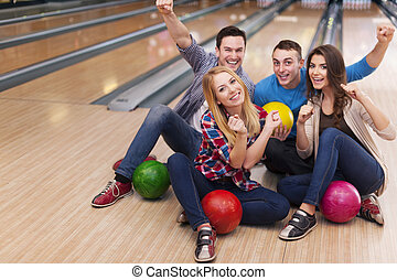 Young group of friends in bowling alley