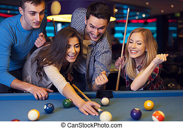 Friends cheering while their friend aiming for billiards...