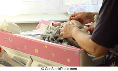 Changing Diapers - Babysitter prepares the child to change...