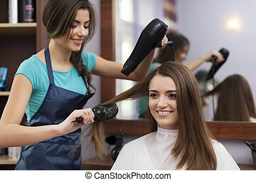Female hairdresser using hairbrush and hair dryer