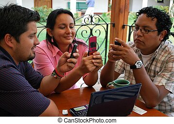 Hispanic friends sending messages on their cell phones