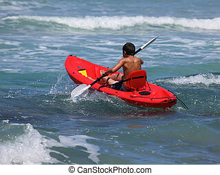 boy rowing in sea kayak
