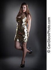 Seductive young girl posing in shiny golden dress